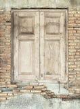 Hölzerne Fenster auf Backsteinmauer Stockbild