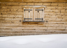 Hölzerne Fensterläden auf einem Kabinenfenster mit Schneewehe im forground Stockbilder