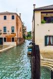 Hölzerne festmachende Pfosten und angekoppelte Boote entlang Seiten eines Wasserstraßen-/Wasserkanals in Venedig, Italien stockfotografie