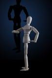 Hölzerne Figürchen, die Muskeln in der Bodybuilderhaltung mit Schatten biegt Stockfotografie