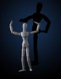 Hölzerne Figürchen, die Muskeln in der Bodybuilderhaltung mit Schatten biegt Stockfotos