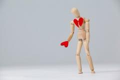 Hölzerne Figürchen mit einem defekten Herzen und dem Halten eines roten Herzens Stockbild