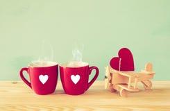 Hölzerne Fläche mit Herzen nahe bei Paaren von coffe Schalen Lizenzfreie Stockfotografie