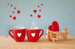 Hölzerne Fläche mit Herzen nahe bei Paaren von coffe Schalen Lizenzfreie Stockbilder