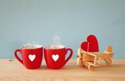 Hölzerne Fläche mit Herzen nahe bei Paaren von coffe Schalen Stockbild