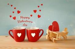 Hölzerne Fläche mit Herzen nahe bei Paaren von coffe Schalen Lizenzfreie Stockfotos