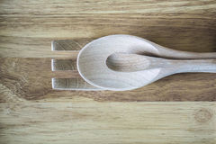 Hölzerne Gabel, Löffel und wenig Löffel auf Holzoberfläche stockfotos