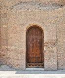 Hölzerne gealterte gewölbte Tür des Schmutzes auf Steinziegelsteinwand Lizenzfreie Stockfotografie