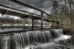 Hölzerne gehende Brücke über Winter-Wasserfall Stockfoto