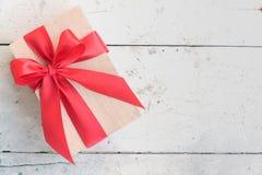 Hölzerne Geschenkbox mit rotem Bandbogen auf Weinlesehintergrund Lizenzfreie Stockbilder