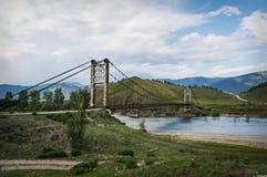 hölzerne Hängebrücke über einem Gebirgsfluss stockfotografie