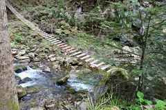 Hölzerne Hängebrücke in den Bergen lizenzfreie stockbilder
