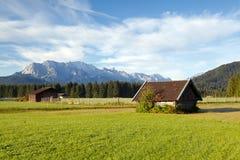 Hölzerne Hütten auf alpinen Wiesen, Deutschland Stockfotografie