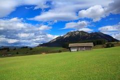 Hölzerne Hütten auf grünen Wiesen in den Alpen Stockfotografie