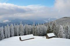 Hölzerne Hütten in den Winterbergen Lizenzfreies Stockbild