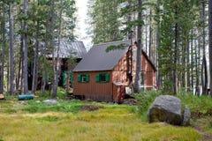 Hölzerne Hütten im Wald lizenzfreies stockbild
