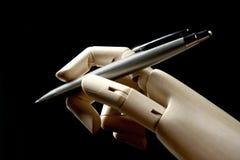 Hölzerne Hand des Mannequins mit einer Feder zum zu schreiben Stockfotos