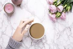 Hölzerne Hand, Kaffee und rosa Blumen auf Marmorhintergrund stockfotografie