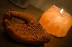 Hölzerne Hand mit Henna Engravings und einer Himalajasteinsalz-Kerze stockfoto