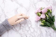 Hölzerne Hand mit rosa Blumen auf Marmorhintergrund lizenzfreies stockfoto