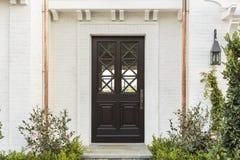 Hölzerne Haustür des weißen Ziegelsteinhauses mit Anlagen Lizenzfreies Stockbild