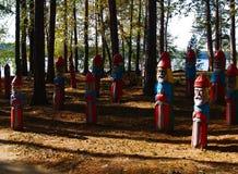 Hölzerne Heldskulpturen auf Herbstwald Stockfotografie
