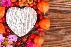 Hölzerne Herz- und Herbstfrüchte stockfoto