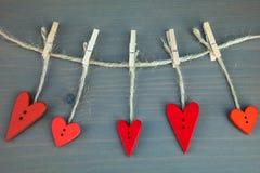 Hölzerne Herzen auf Ñ- lothespins auf grauem hölzernem Hintergrund Stockfotografie