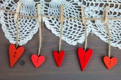 Hölzerne Herzen auf Ñ- lothespins auf grauem hölzernem Hintergrund mit Spitze Stockbilder