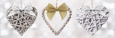 Hölzerne Herzen geflochten mit dem Bandbogen lokalisiert auf dem Silber verwischt Lizenzfreie Stockfotografie