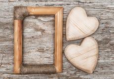 Hölzerne Herzen und Rahmen auf dem alten Holz stockbilder
