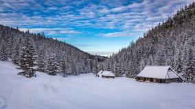 Hölzerne Hochlandhäuser des Winters bei Sonnenuntergang Stockbild