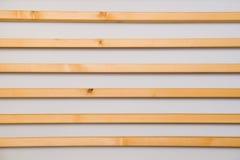 Hölzerne horizontale Latten batten auf einem hellgrauen Wandhintergrund Innendetail, Beschaffenheit, Hintergrund Das Konzept des  stockbild