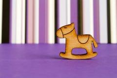 Hölzerne Ikone des Schaukelpferds der Kinder auf purpurrotem gestreiftem backgr Stockbild