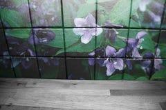 Hölzerne Küchenarbeitsplatte vor Küchenfliesen mit purpurroten Blumen auf ihnen stockfoto