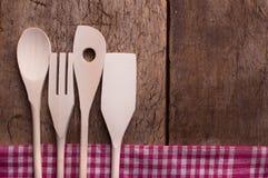 Hölzerne Küchengeräte auf hölzernem Hintergrund Stockfotografie
