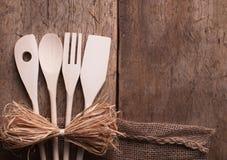 Hölzerne Küchengeräte auf hölzernem Hintergrund Stockfotos