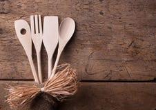 Hölzerne Küchengeräte auf hölzernem Hintergrund Stockfoto