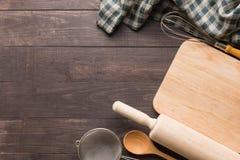 Hölzerne Küchenwerkzeuge und -serviette auf dem hölzernen Hintergrund Stockbilder