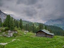 Hölzerne Kabine in den bayerischen Alpen mit stürmischem Wetter im Hintergrund stockbild