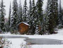 Hölzerne Kabine im magischen Schnee bedeckte Wald Stockfotos