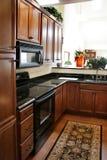Hölzerne Kabinette der Küche schwarz und nicht rostender Ofen Stockbilder