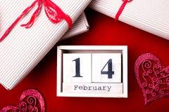 Hölzerne Kalendershow vom 14. Februar mit rotem Herzen und Geschenkboxen Stockfotografie