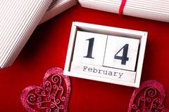 Hölzerne Kalendershow vom 14. Februar mit rotem Herzen und Geschenkboxen Stockbild