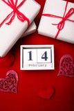 Hölzerne Kalendershow vom 14. Februar mit rotem Herzen und Geschenkboxen Stockbilder