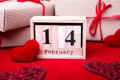 Hölzerne Kalendershow vom 14. Februar mit rotem Herzen und Geschenkboxen Lizenzfreies Stockfoto