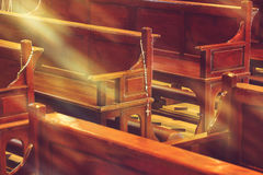 Hölzerne Kirchenbänke in der Kirche und in den Rosenkranzperlen Lizenzfreies Stockfoto