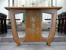 Hölzerne Kirchentabelle eingeschrieben mit den Wörtern eins in Christus stockfotos