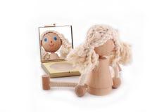Hölzerne kleine Puppe mit den blauen Augen, die im Spiegel schauen Stockbilder