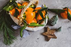 Hölzerne Korb-Mandarine mit Blättern und Lichtern, Tangerine-Orange auf Gray Table Background Christmas New-Jahr-Dekors lizenzfreies stockbild